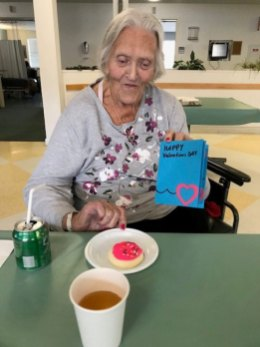 San Simeon female resident holding up Valentine's Day card while eating decorated cookie