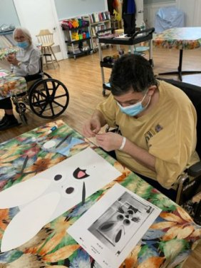 male San Simeon resident creating Easter art with paper