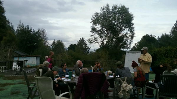 People sitting at an outside table with an instructor standing near a flipchart.