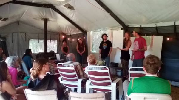 Students in the Permaculture Design Certificate Course present their final design to the class in a tent at the NEST.