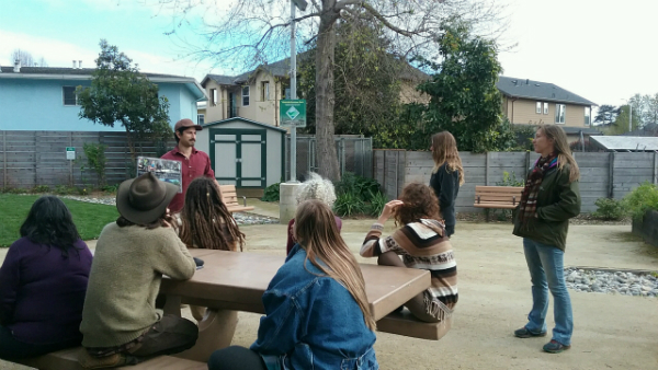 People sitting at a table in a park while a person presents about the community orchard project.