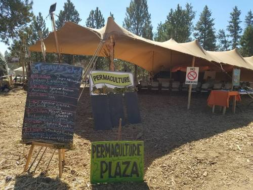 Tent at a festival with signs reading Permaculture Plaza