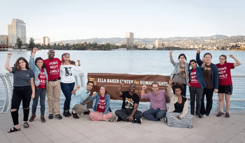 Thirteen people, some sitting and others standing, surround an Ella Baker Center for Human Rights banner in front of Lake Merritt. Their fists are raised.