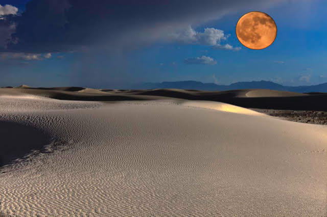 Orange moon suspended over White Sands, New Mexico