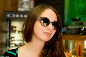 A photo of Alicia in the1960's inspired sunglasses by Barton Perreira.