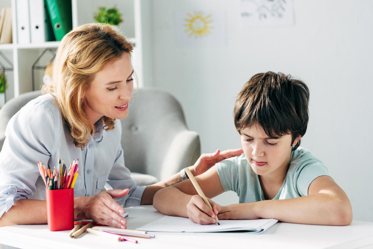 Enfant avec le dessin de dyslexie avec le crayon et le psychologue d'enfant le regardant