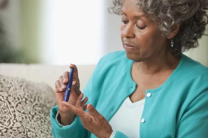Une femme vérifie son niveau de sucre dans le sang .. Blend Images - Jose Luis Pelaez Inc / Getty Images