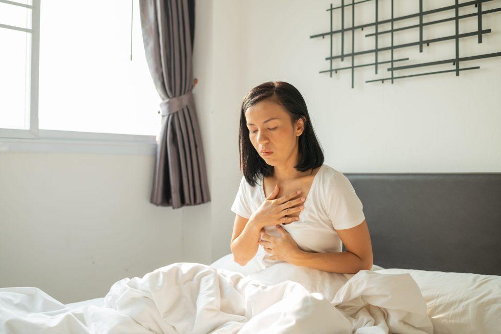 Femme assise dans son lit prise de nausées de grossesse