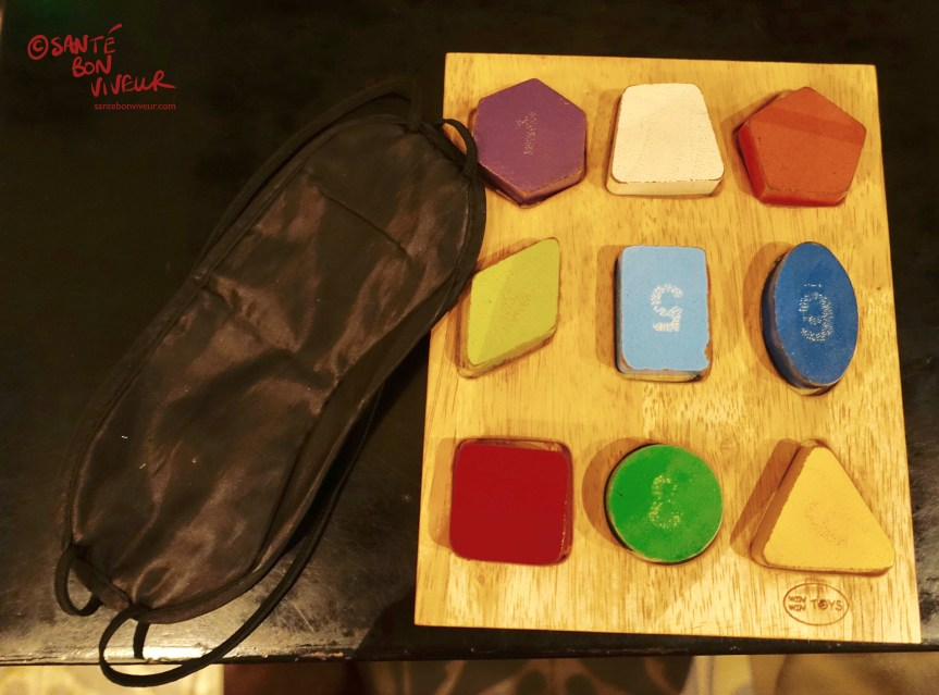 Wooden shapes puzzle & blindfold used as an acclimatisation exercise for feeling youry way around the dining table in the dark! At Noir. Dining in the Dark Restaurant, Saigon/Ho Chi Minh City, Vietnam 2017