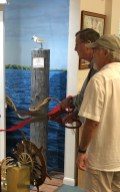 CIHS Past President Jim Pigott cuts the ribbon the updated Santiva Mailboat Gallery at the Captiva Library