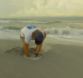 SCCF Biologist Jack Brzoza digging. Photo by Tom James of Pelican Media