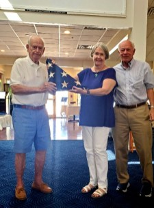 Commodore Maggie Davis (center) presenting the flag to Gib Warren (left), joined by Jack Tukey.