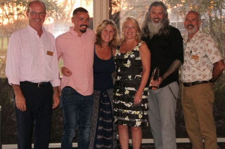 Past chair Brian Kautz (left) and incoming chair Mark Blust (right) present Paper Fig Kitchen's crew with the New Business of the Year Award: Dylan Trafton, Karan Balmer, and owners Jeramie and Debra Campana.