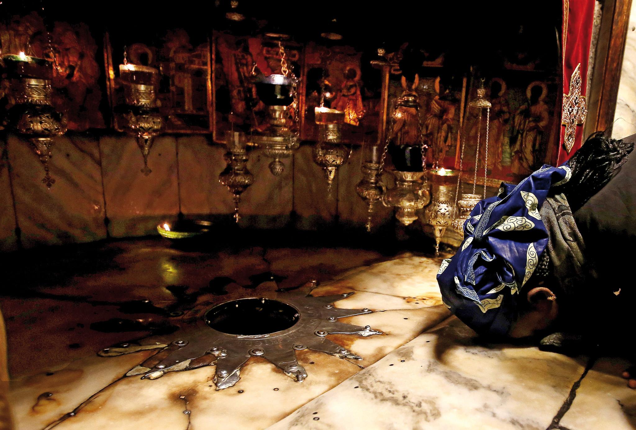 Uma pessoa reza diante da estrela sagrada, que marca o lugar onde se crê ter nascido Jesus. Cripta da Igreja da Natividade, Belém, na Cisjordânia, 5 de dezembro de 2016. EPA / ABED AL HASHLAMOUN