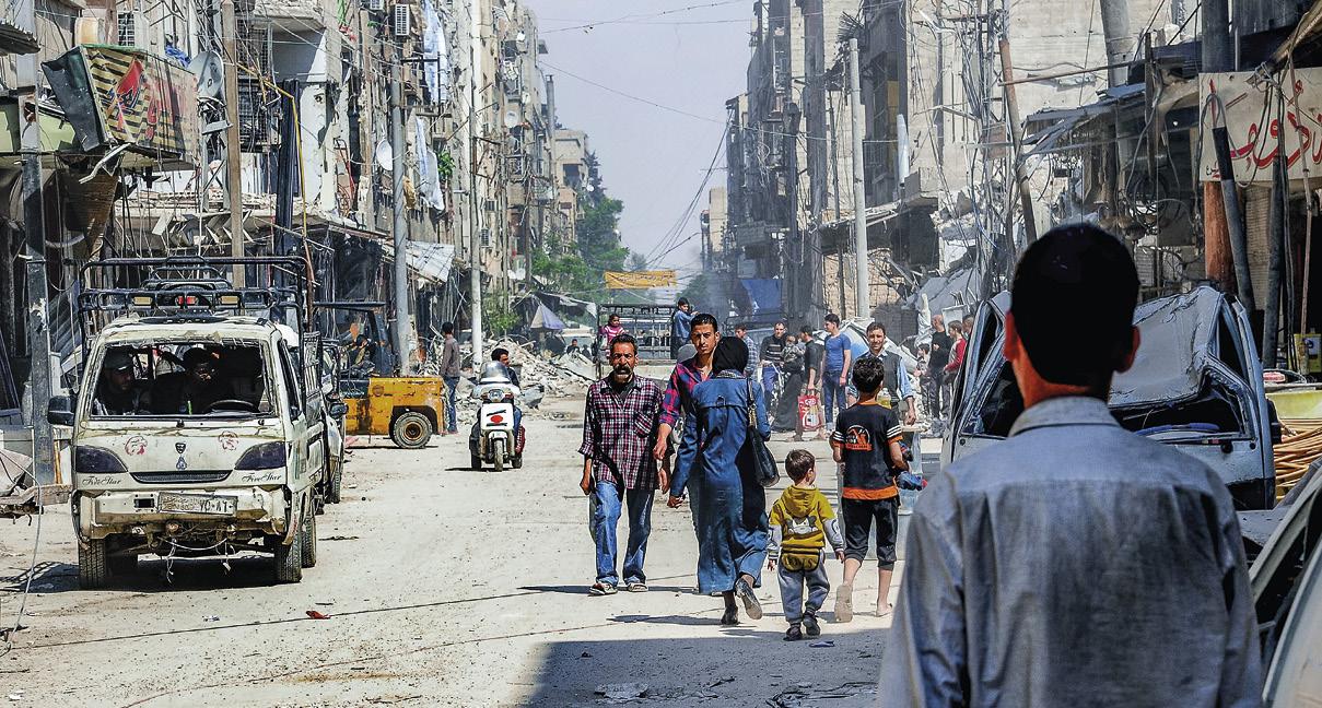Cidadãos sírios caminhando ao lado de prédios danificados na cidade de Douma, no leste de Ghouta, na zona rural de Damasco, Síria, 15 de abril de 2018. EPA/SANA.