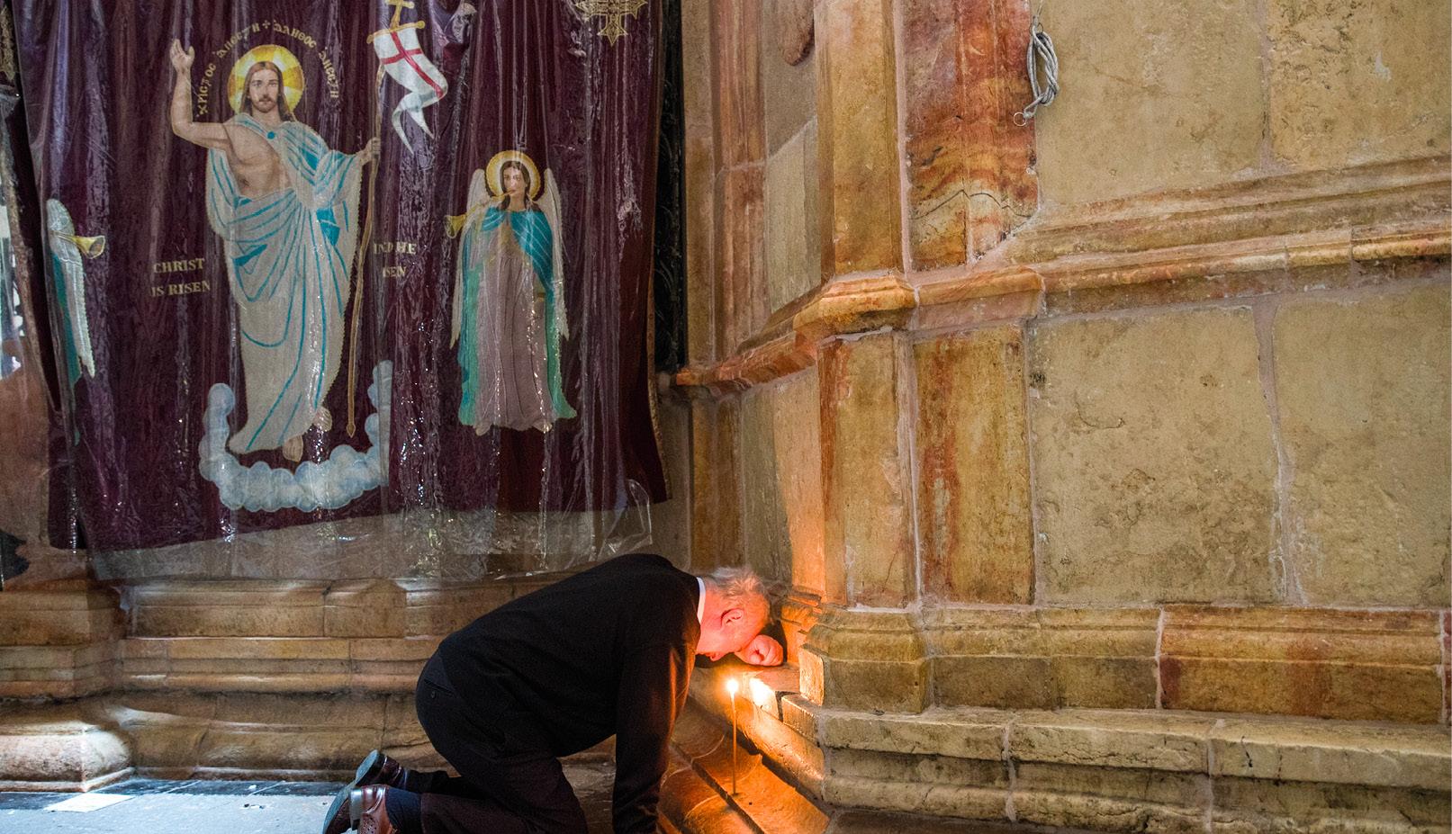 Um homem reza no lugar onde se acredita que Jesus terá sido sepultado. Igreja do Santo Sepulcro, Cidade Velha de Jerusalém. EPA / ATEF SAFADI