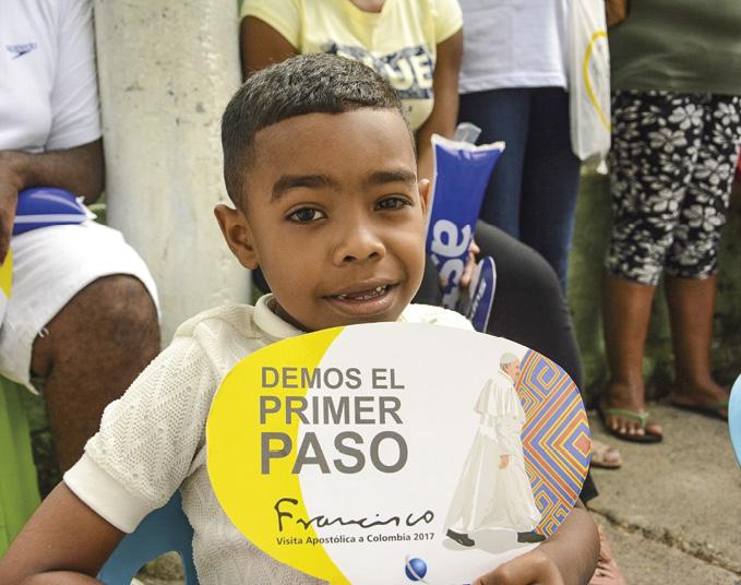 Visita Apostólica do Papa Francisco à Colômbia, em 2017. Criança empunhando cartaz: DEMOS O PRIMEIRO PASSO.