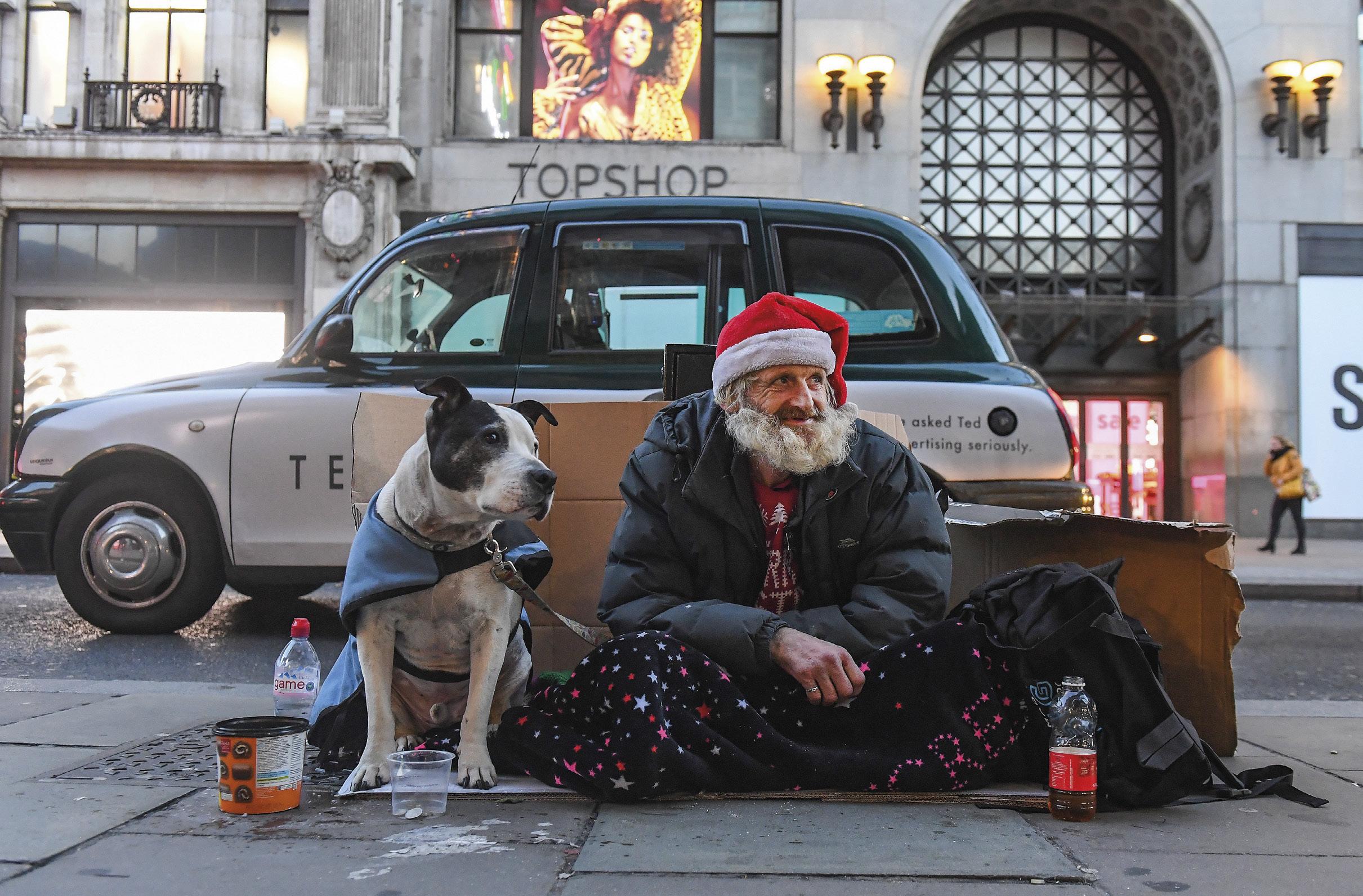 """Francisco, 56 anos, e o seu Terrier, Milo, há 8 anos na rua, depois de ter perdido o filho e de ter brigado com a companheira. """"Merdas acontecem na vida"""". Francisco faz parte dos ceca de 25 mil sem abrigo, no Reino Unido. EPA/ANDY RAIN"""