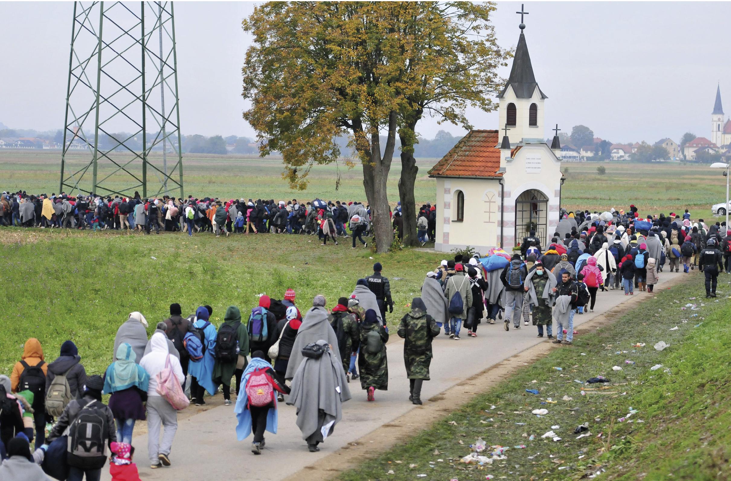 Migrantes a caminho do centro de acolhimento de refugiados em Dobova, Eslovénia, 23 de outubro de 2015. Mais de 680 mil migrantes e refugiados chegaram ao continente europeu, por mar, só em 2015, o maior movimento populacional desde a Segunda Guerra Mundial. EPA / IGOR KUPLJENIK