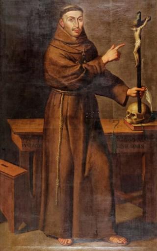 Frei António das Chagas apontando para o crucifixo - em cima da mesa uma caveira.