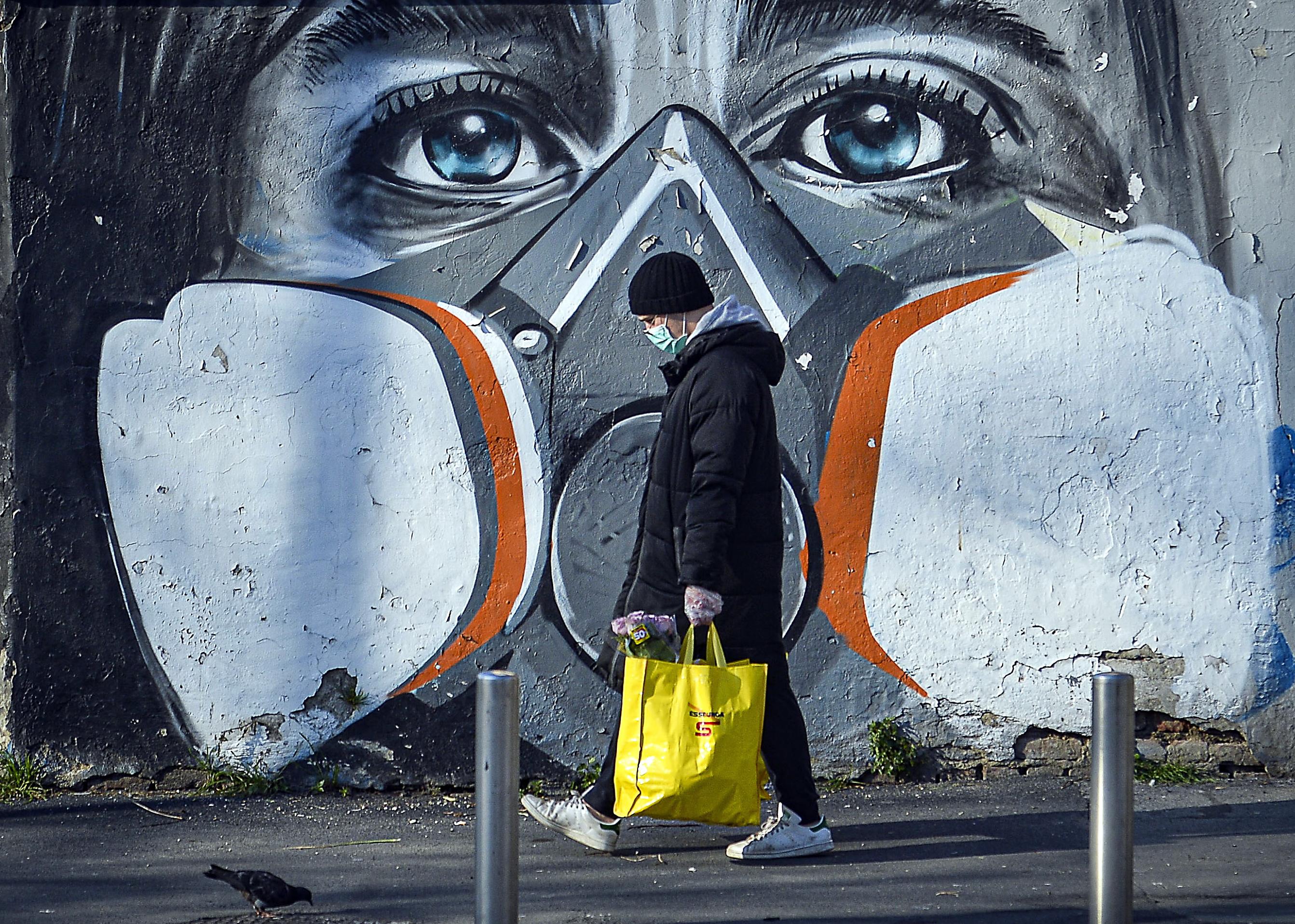 Um homem anda com suas compras ao lado de uma pintura mural que retrata uma pessoa usando uma máscara de gás, Milão, Itália, 16 de março de 2020. A Itália está trancada na tentativa de impedir a propagação do pandêmico Coronavírus. Vários países europeus fecharam fronteiras, escolas e instalações públicas e cancelaram a maioria dos principais eventos esportivos e de entretenimento, a fim de impedir a propagação do coronavírus SARS-CoV-2, causando a doença Covid-19. EPA / ANDREA FASANI