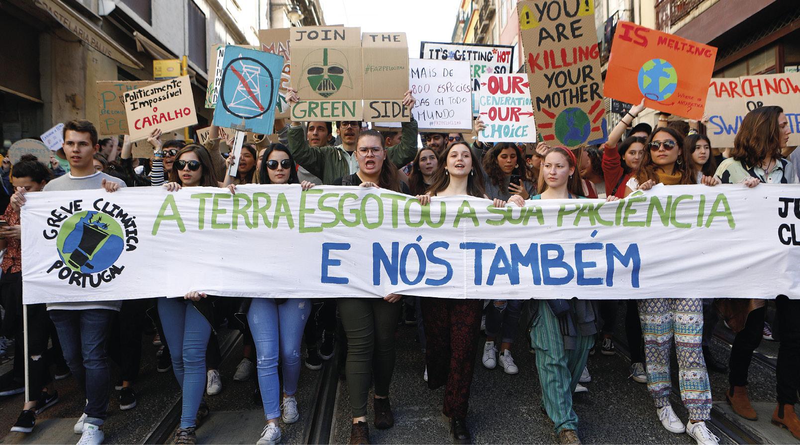 """Estudantes portugueses associados ao movimento """"Greve à Escola pelo Clima"""", exibem uma faixa onde se lê """"A Terra Esgotou A sua Paciência - E Nós Também"""" durante uma manifestação para exigir que a crise climática seja uma prioridade governamental, Lisboa, 15 de março de 2019. Foto António Pedro Santos/LUSA."""
