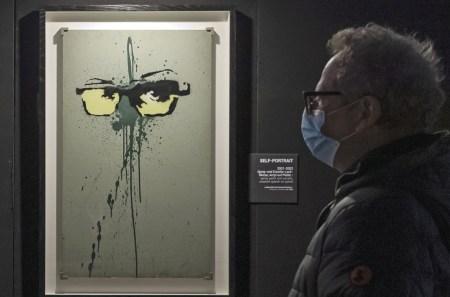 Auto-retrato (2001-2002) do artista de rua britânico, Banksy, exposição Construindo Castelos no Céu, Basel, Suíça, 1 de março de 2021. Foto EPA / GEORGIOS KEFALAS.