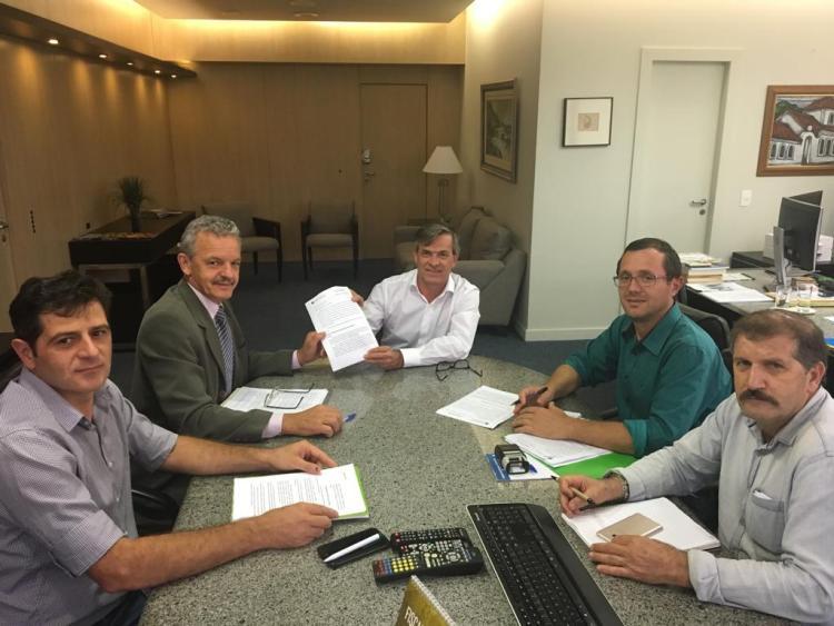 Secretário da Fazenda, Paulo Eli, entre cópia do documento de adesão do Estado a isenção do ICMS da autogeração de energia
