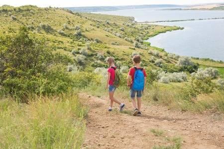 81813880-adolescente-menino-menina-com-mochilas-ligado-a-costas-ir-ligado-um-caminhada-viagem-bonito-paisagem