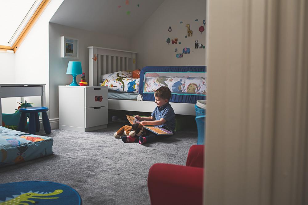 boy sitting on bedroom floor enjoying a book
