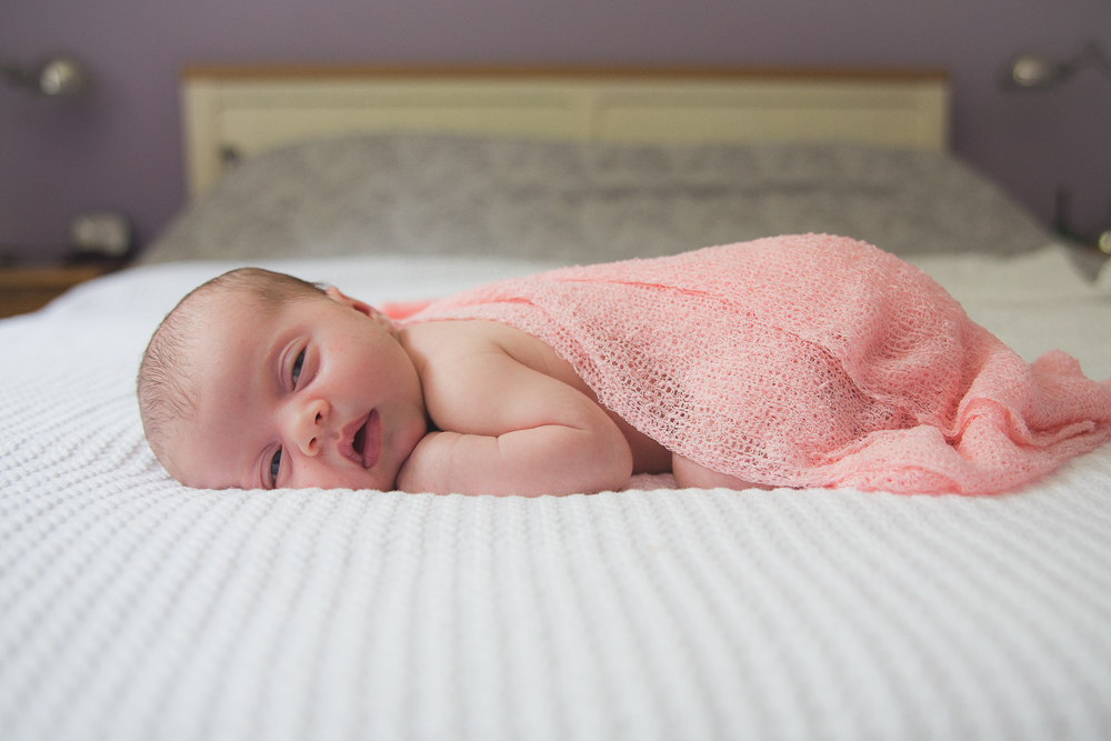 sleepy newborn baby stomach tummy belly pink blanket