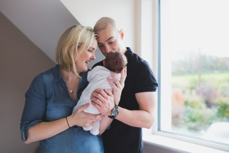 father, mother and baby portrait, newborn photography, window, smiling