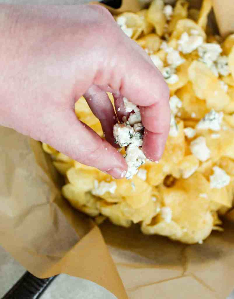 hand dropping blue cheese crumbles onto chips