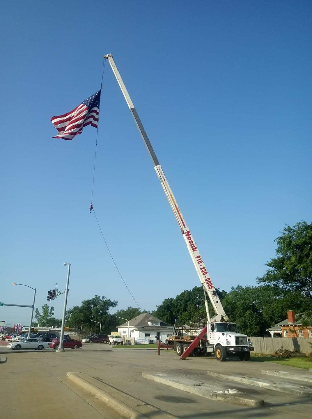 A crane holds a large American flag near intersection of Mission and Line Streets as a symbol for the community spirit that happened after the tornadoes struck Sapulpa Memorial Day Weekend.