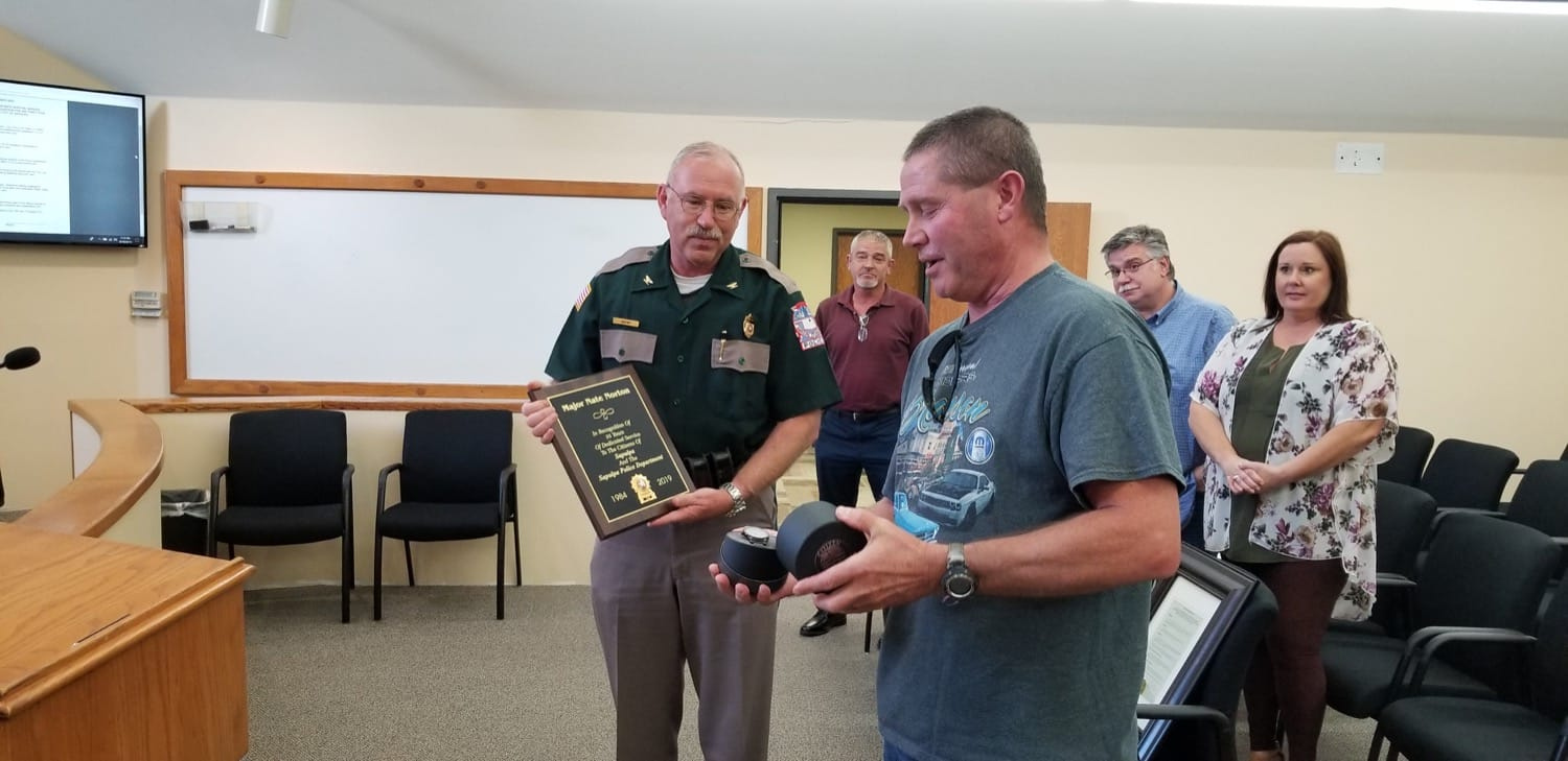 Police Chief Haefner (left) presents a plaque to Major Nate Norton (right) in honor of his 35 years of service.
