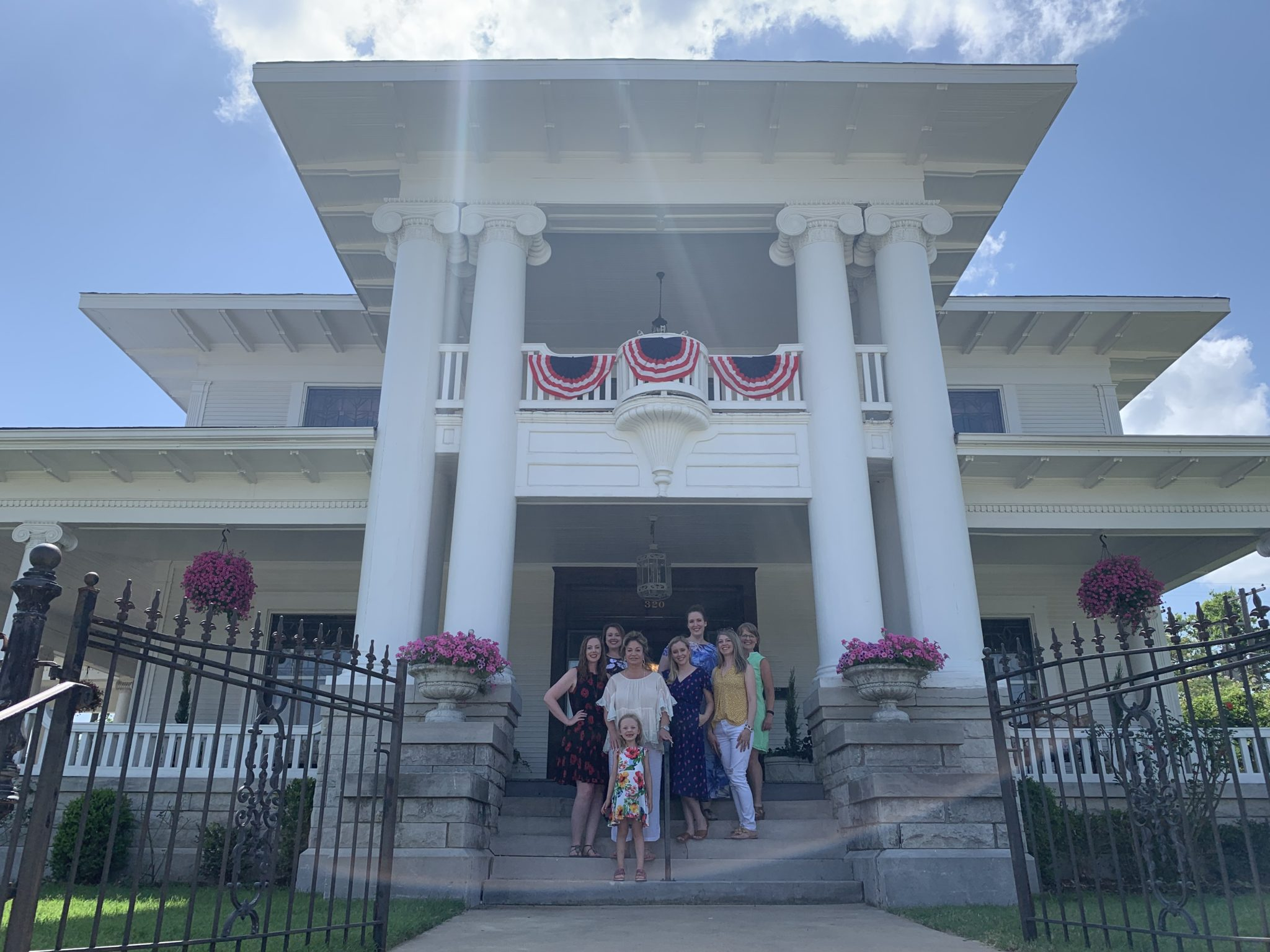 SeneGence members and executives announcing the purchase of the Burnett Mansion last June. Left to Right: Christin Slough, Amanda Chioto, Joni Rogers with Lily Slough, Heather Menke, Amanda Brown, Jessica Terrill, Vickie Beyer.