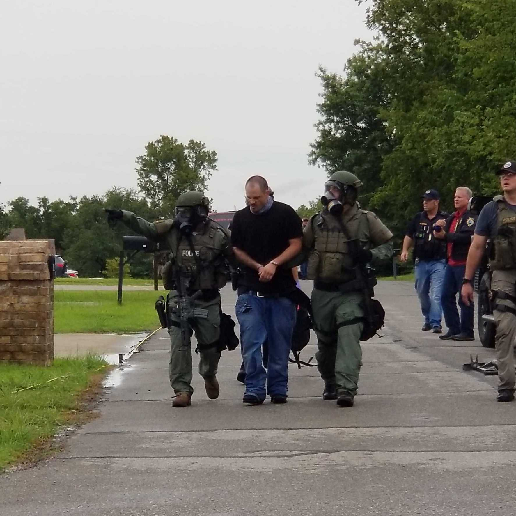 Librao Rosales ls led outside by members of the Southwest Area SWAT Team after a standoff on Friday.