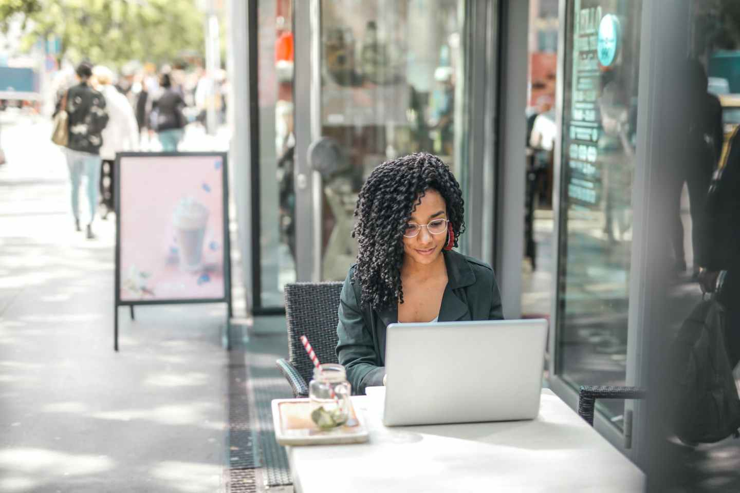 ethnic young woman using laptop while having tasty beverage in modern street cafe
