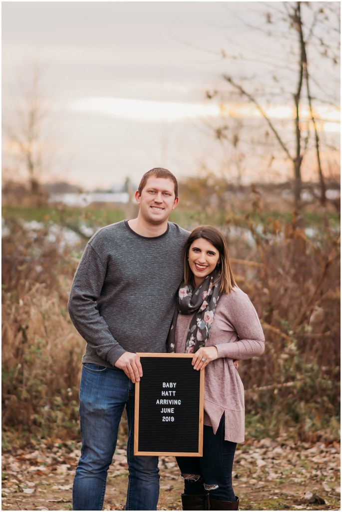 Cute couple holding sign for pregnancy announcement in Michigan