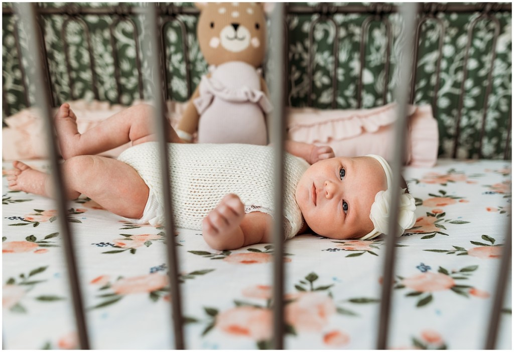 Baby girl laying in crib for Brighton, MI newborn session