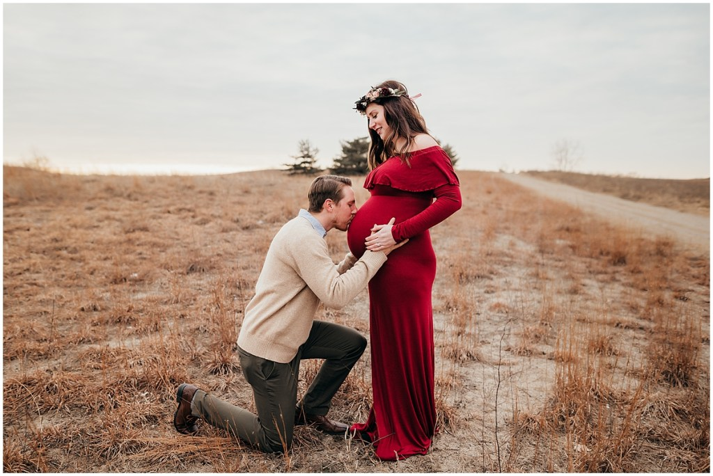 Dad kissing pregnant wife's belly for maternity photo in Brighton