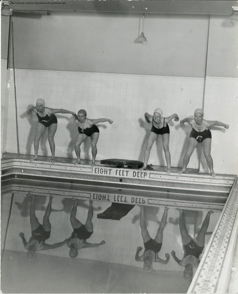Swimmers poised for the start of a race at the women's swimming pool in Fowler Hall, Gallaudet University, Washington, DC. 1950's.
