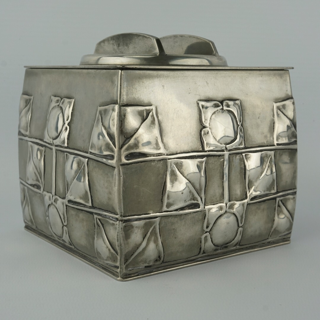 Biscuit box with a Repoussé pattern of stylized flowers.