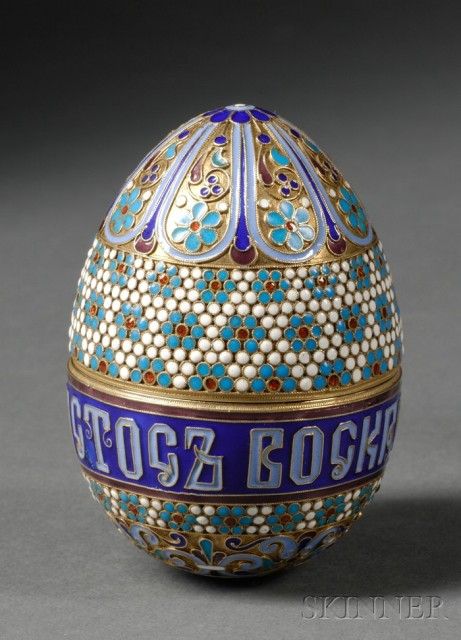 "Easter egg with bud vase interior, gold-washed silver and cloisonne enamel with foliate bands,  a wide band of beaded flowerheads on a white ground. ""Christ is Risen"" lettering in the center over  beaded flowers and scrollwork, opening at center to reveal small bud vase with the inscription ""Easter 1898"" and a monogram. ca. 1898."