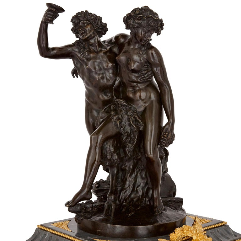 Satyr and female figure, both of whom are engaged in Bacchic revelry (clock detail). Part of a set that also includes a pair of candelabra.
