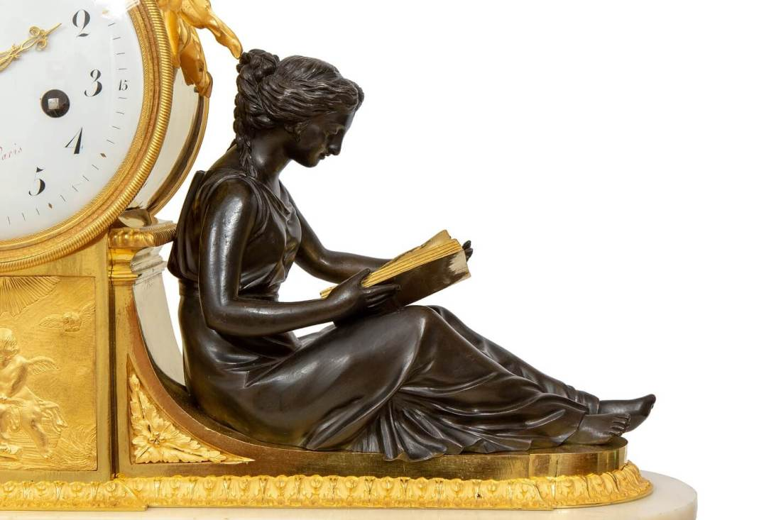 """Mantel clock (Reading lady detail). The clock having an ormolu drum case surmounted by a cast ormolu eagle with a relief below showing two putti holding a bird under a sunburst flanked by two patinated bronze figures, a writing boy and a reading lady. Marble and ormolu base with gadroon feet and with putti holding a mask among scrolling garlands,  flanked by two medallions with female masks. Enamel dial, signed """"Piolaine à Paris"""" in red with gilt brass hands."""