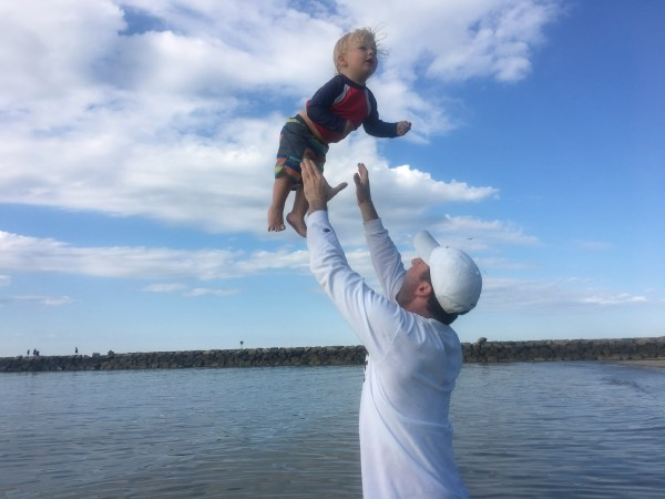 Toddler Being Thrown Into The Air At Beach