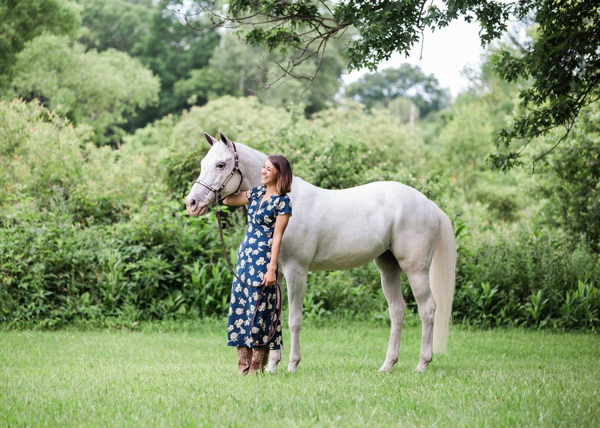 young woman looks at white appaloosa AQHA horse