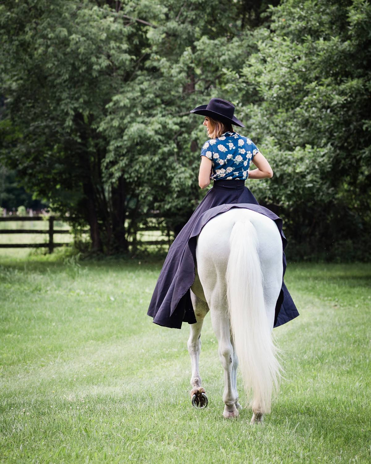 young woman riding white a horse away from camera