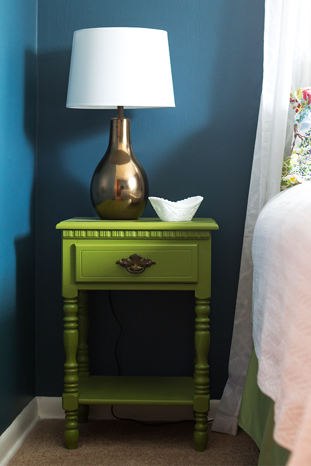 Bright painted night stand and deep teal walls in this simple guest room